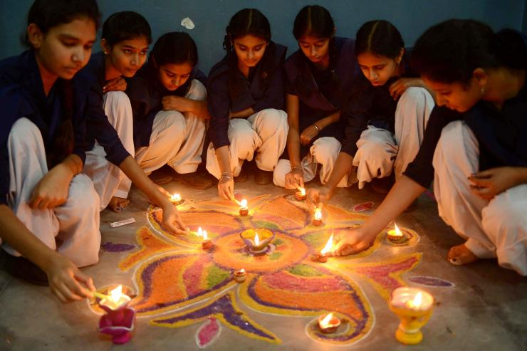 Young Indian Girls Lighting Candles for Diwali