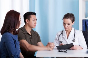 asian couple talking to a doctor about medical results