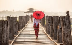 body language of an asian lady holding a red umbrella while crossing a wooden bridge shows confidence