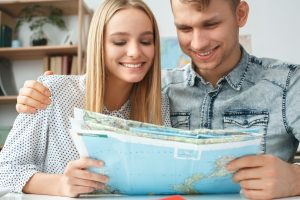 couple holding a map choosing a place to spend their spring vacation