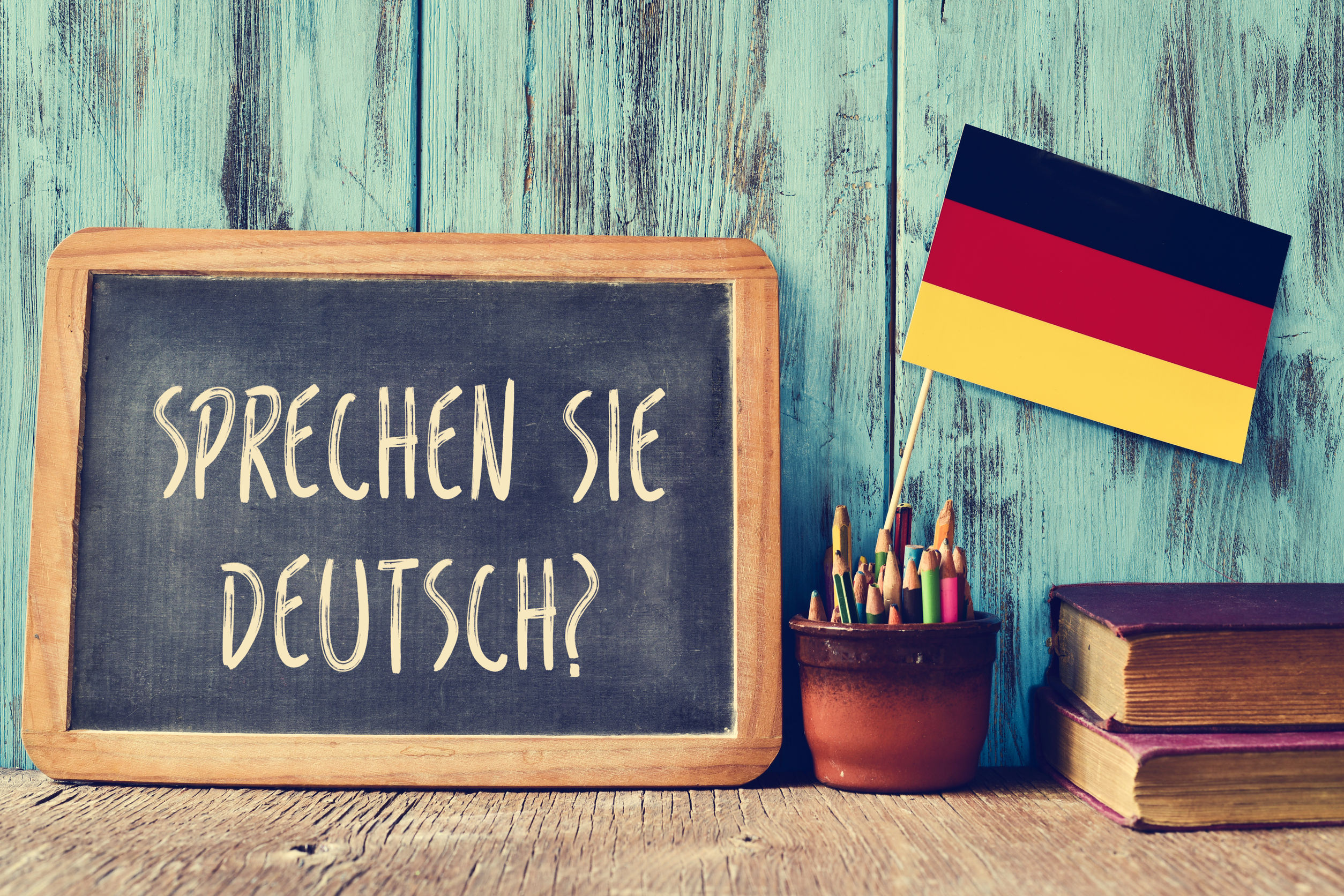 do you speak german written in german language beside a small german flag