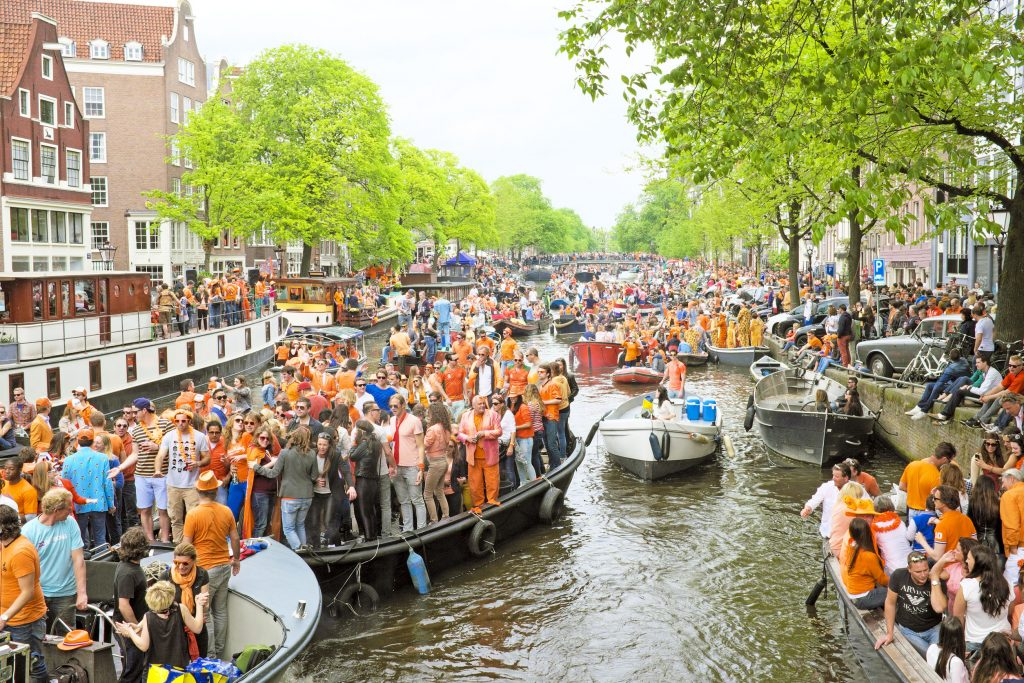 Amsterdam canals full of boats and people in orange during the celebration of kings day