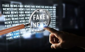 man pointing at the magnified fake news word