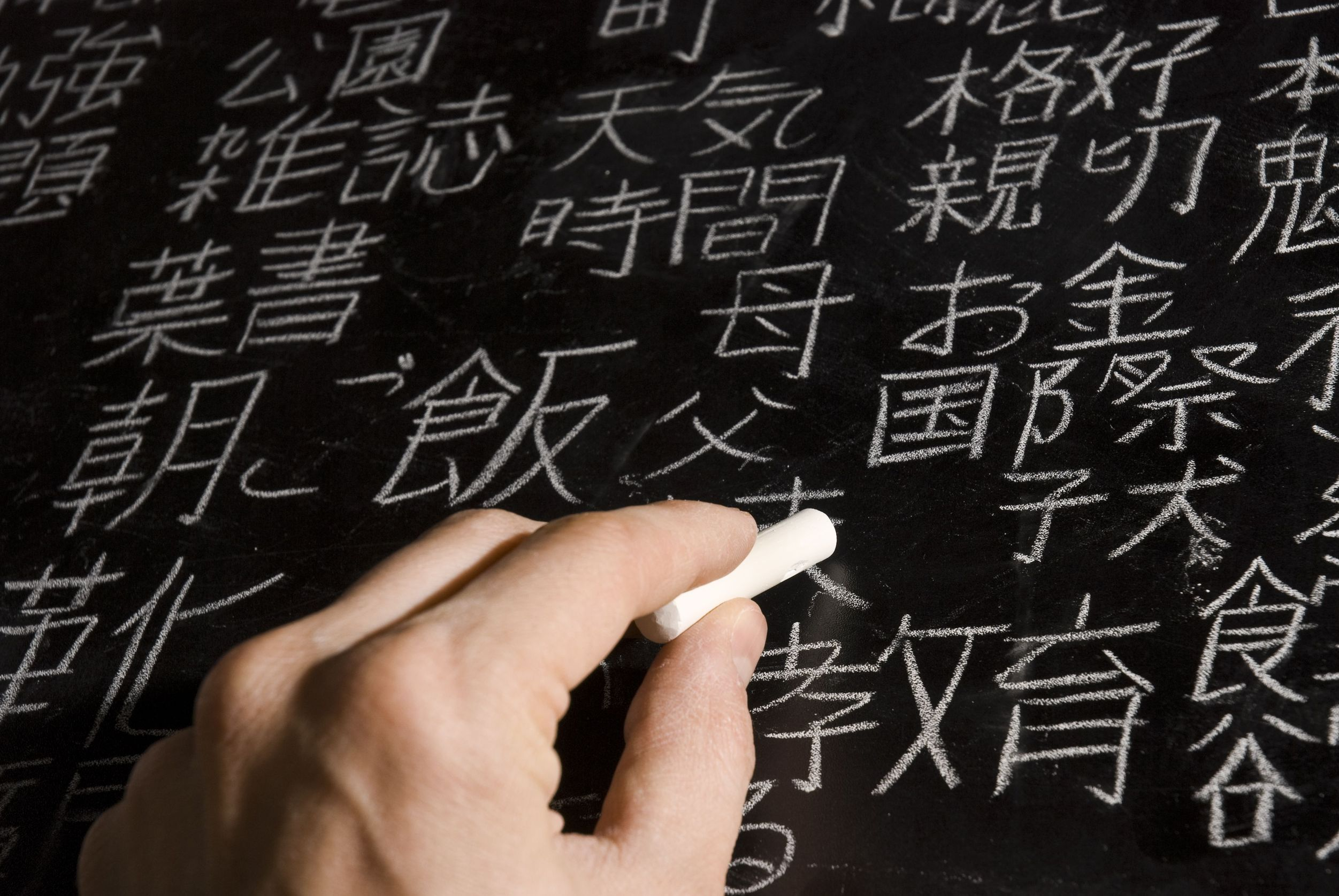 Close up of male hand writing Chinese and Japanese characters on blackboard
