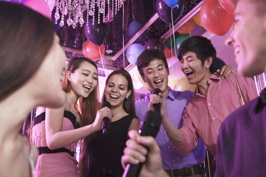 Group of friends holding microphones in a nightclub and singing together karaoke