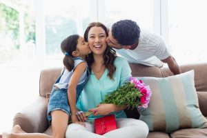 mommy receiving a kiss and flowers from husband and daughter for mothers day