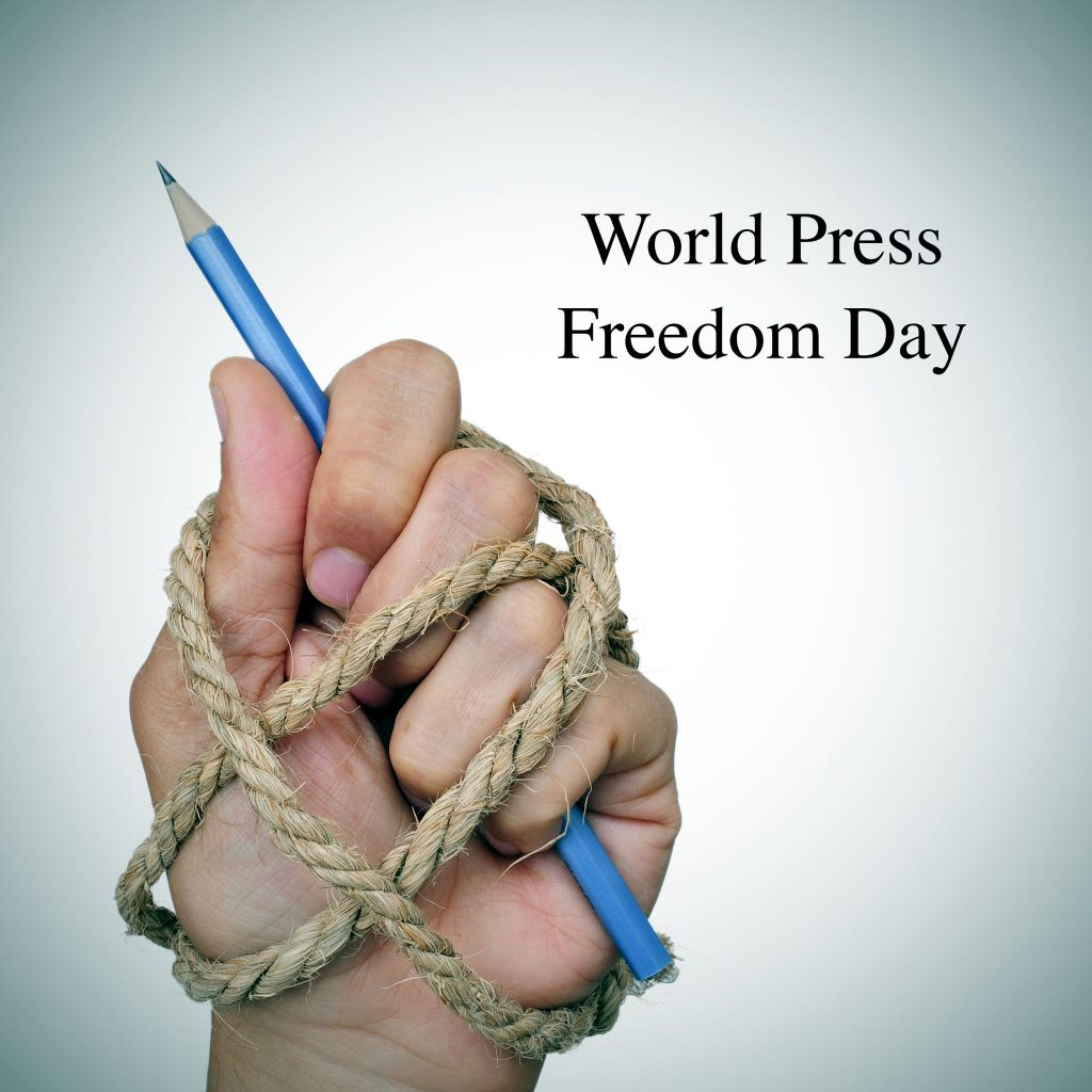 the text world press freedom day and the hand of a man, tied with rope, holding a pencil