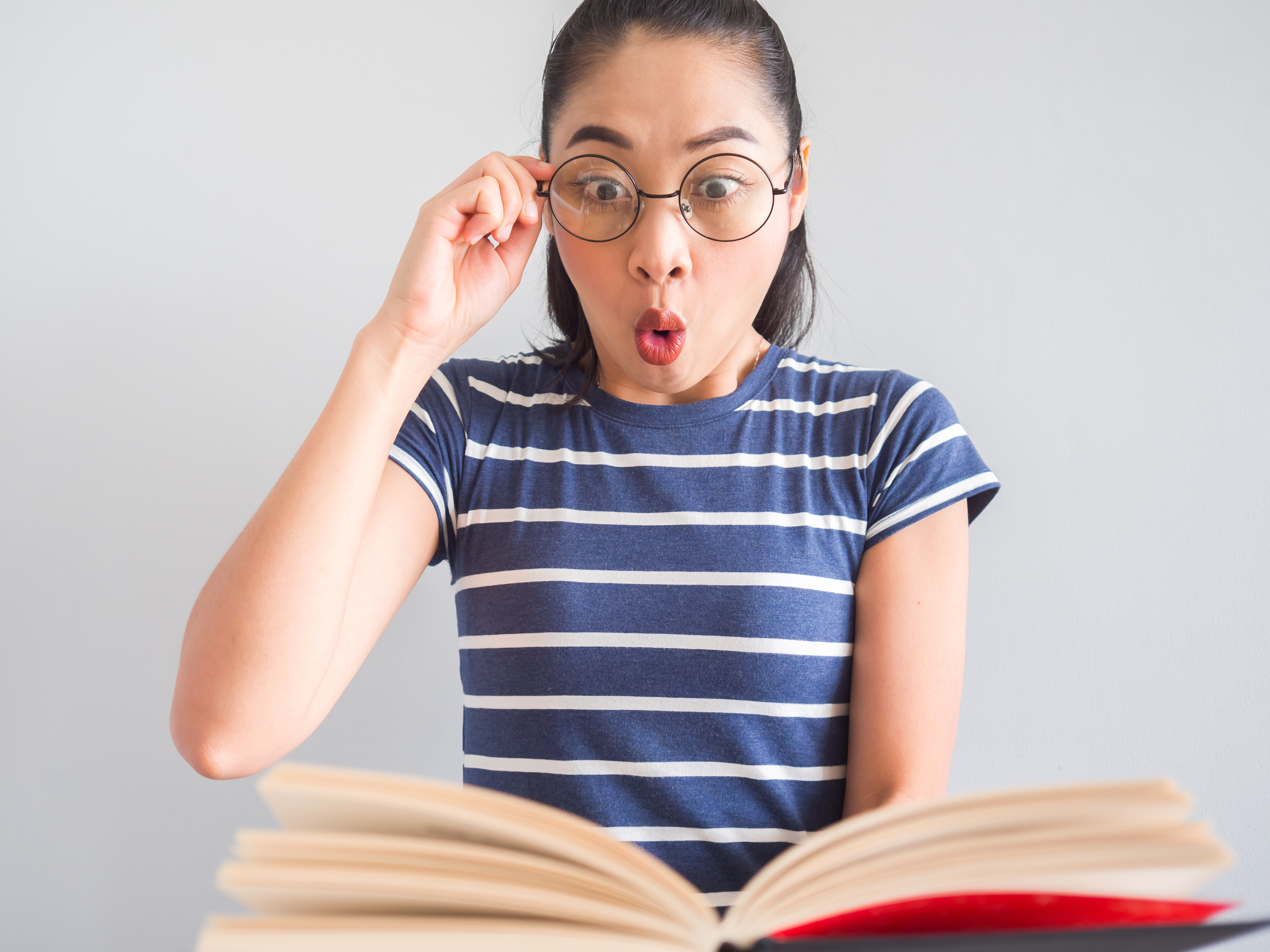 woman with wearing eye glasses got a surprised idea from the book.