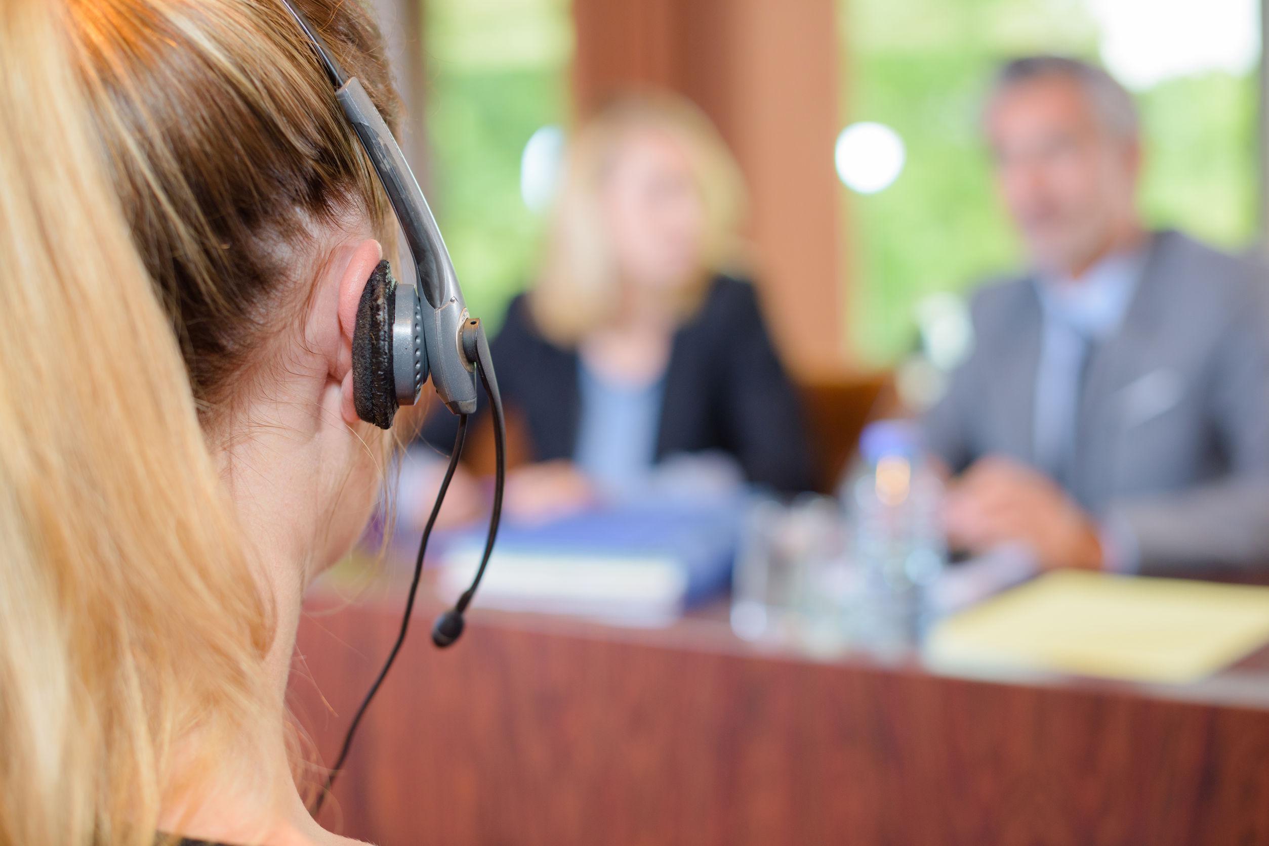 Business Interpreter wearing a head set in a corporate meeting