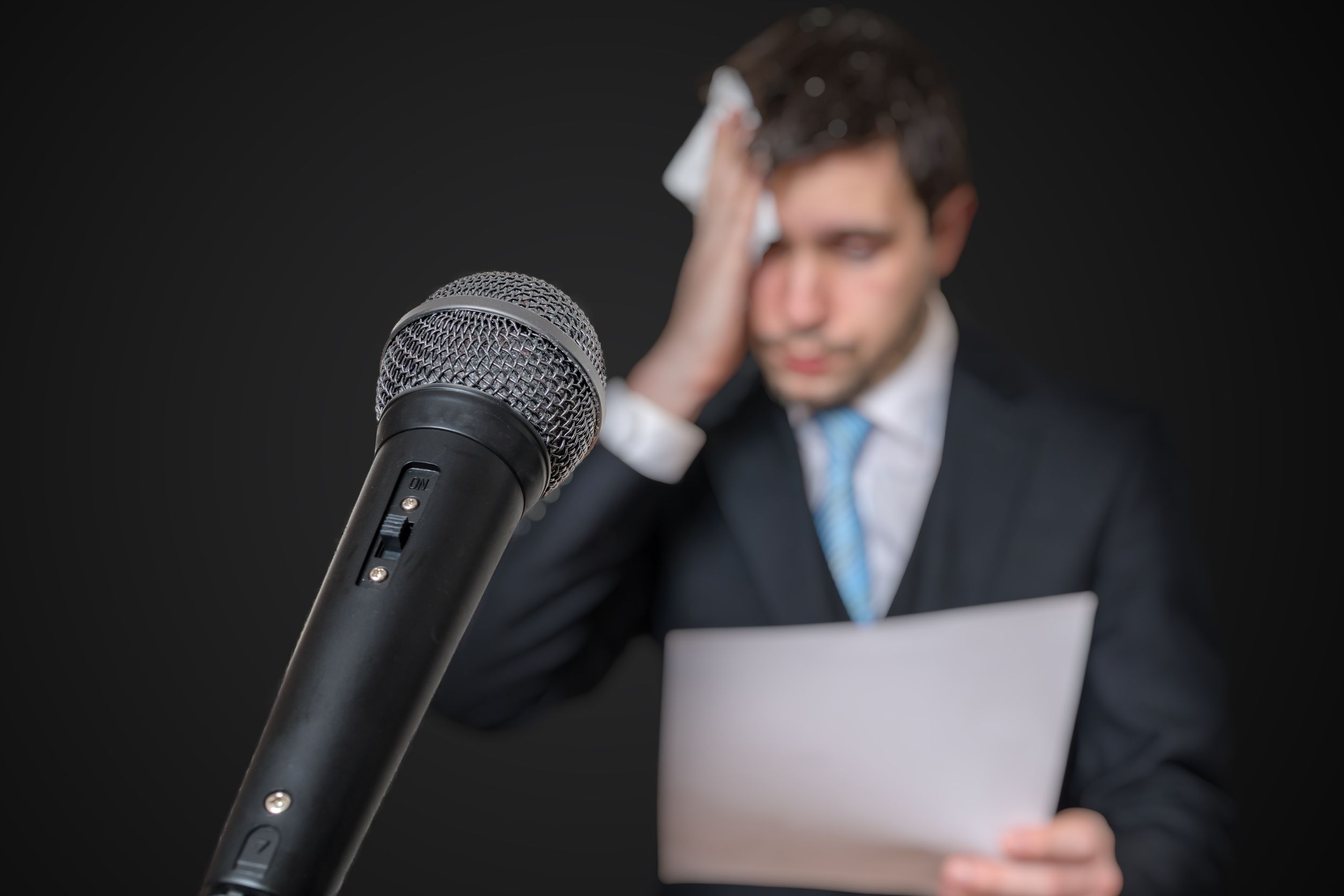 Microphone in front of a nervous man who is afraid of public speech and sweating