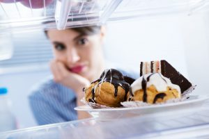 Young hungry woman in front of refrigerator craving chocolate pastries