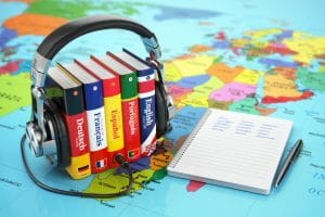 language books bound by a headphone and notebook over a map