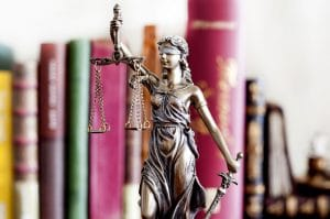 statue of justice in front of books for legal translation
