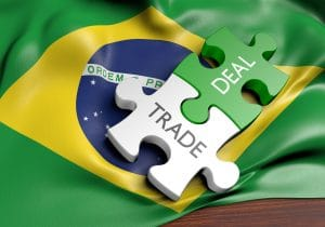 trade and deal puzzle pieces over a brazilian flag