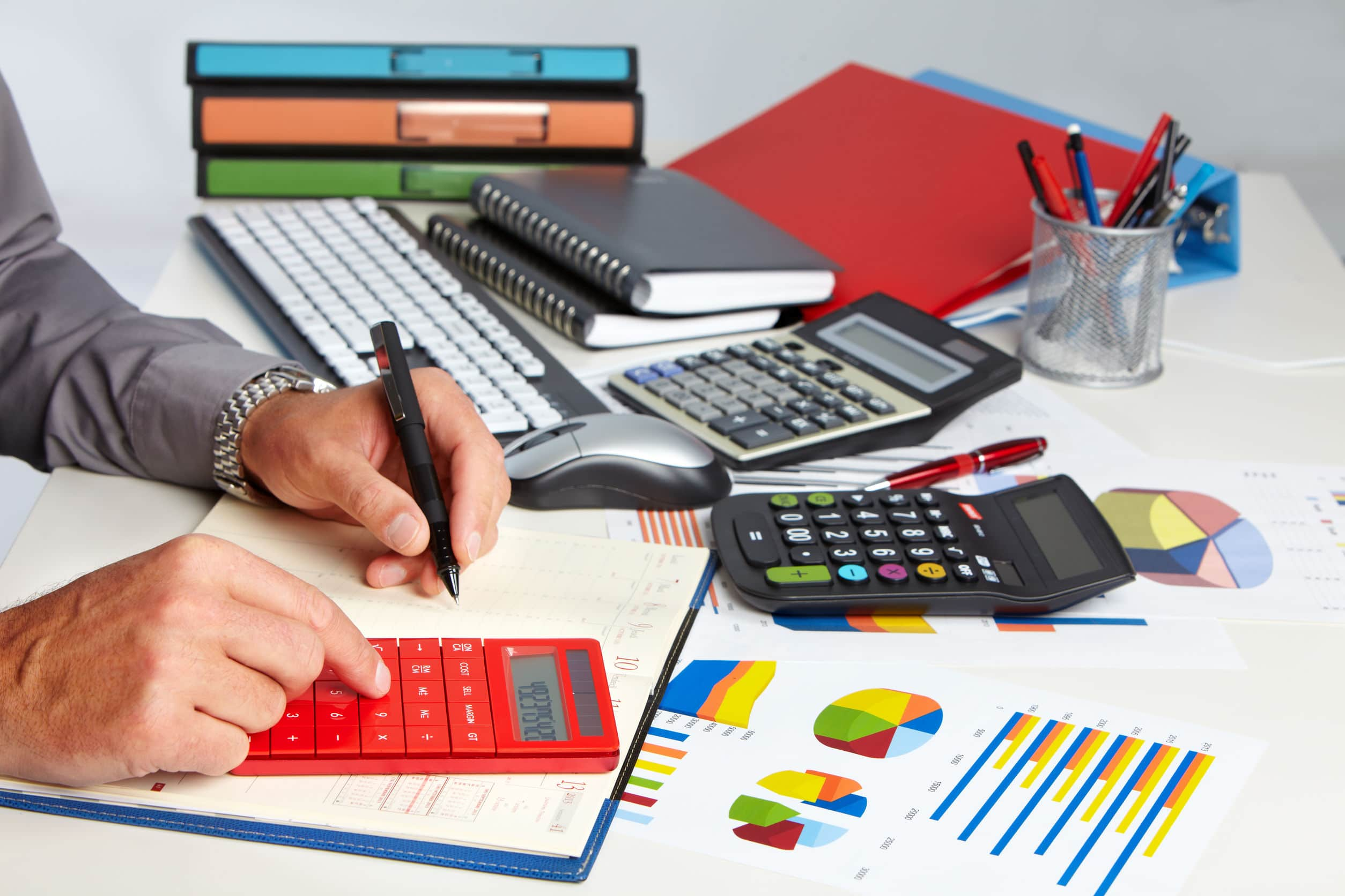 accountant using a calculator while writing results for financial translation