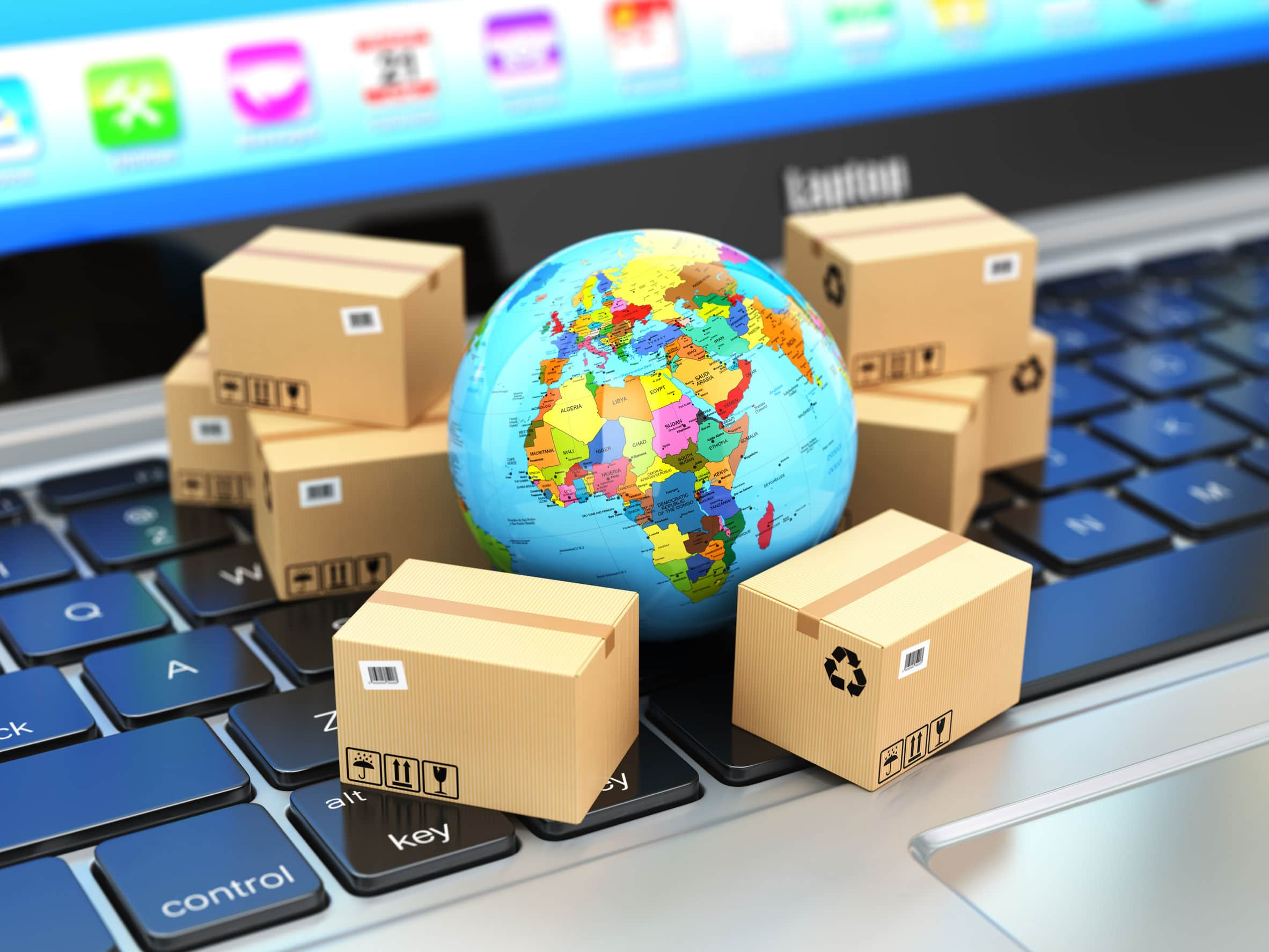 businesses trading globally represented by small boxes around a miniature globe on top of a keyboard
