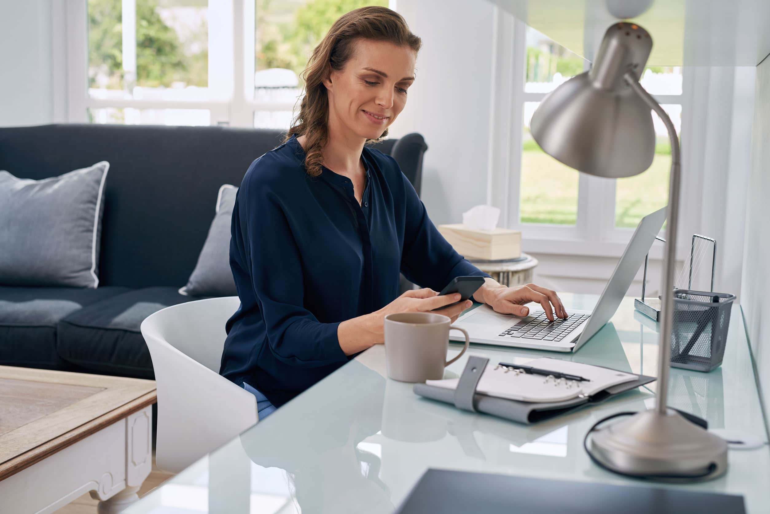 female home-based worker using her monile phone and laptop to earn
