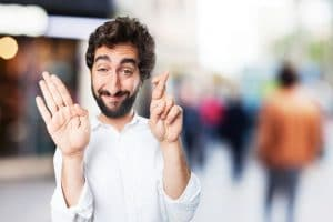 funny young man showing an open palm and a hand with finger crossed