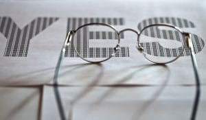 glasses and printed text on white paper