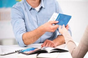 man handing over his passport and plane ticket to a lady