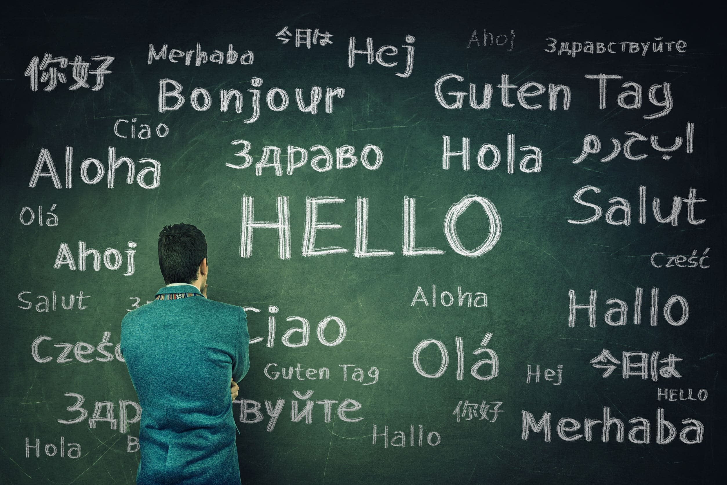 businessman in front of a huge chalkboard written with the word hello in different languages.
