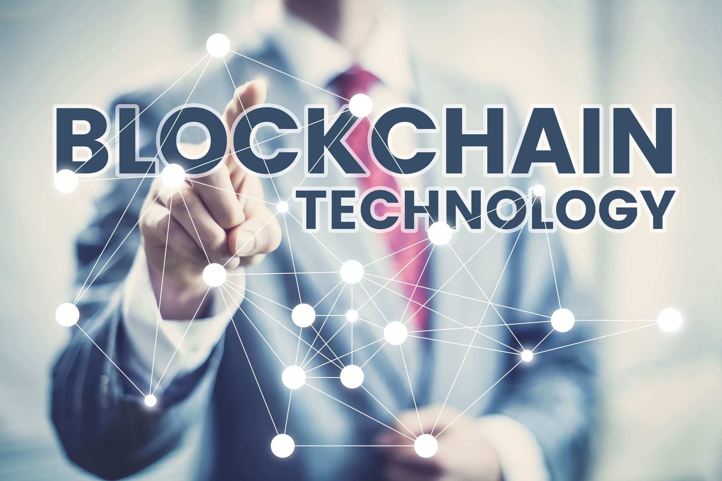 businessman pressing a dot on a blockchain technology banner