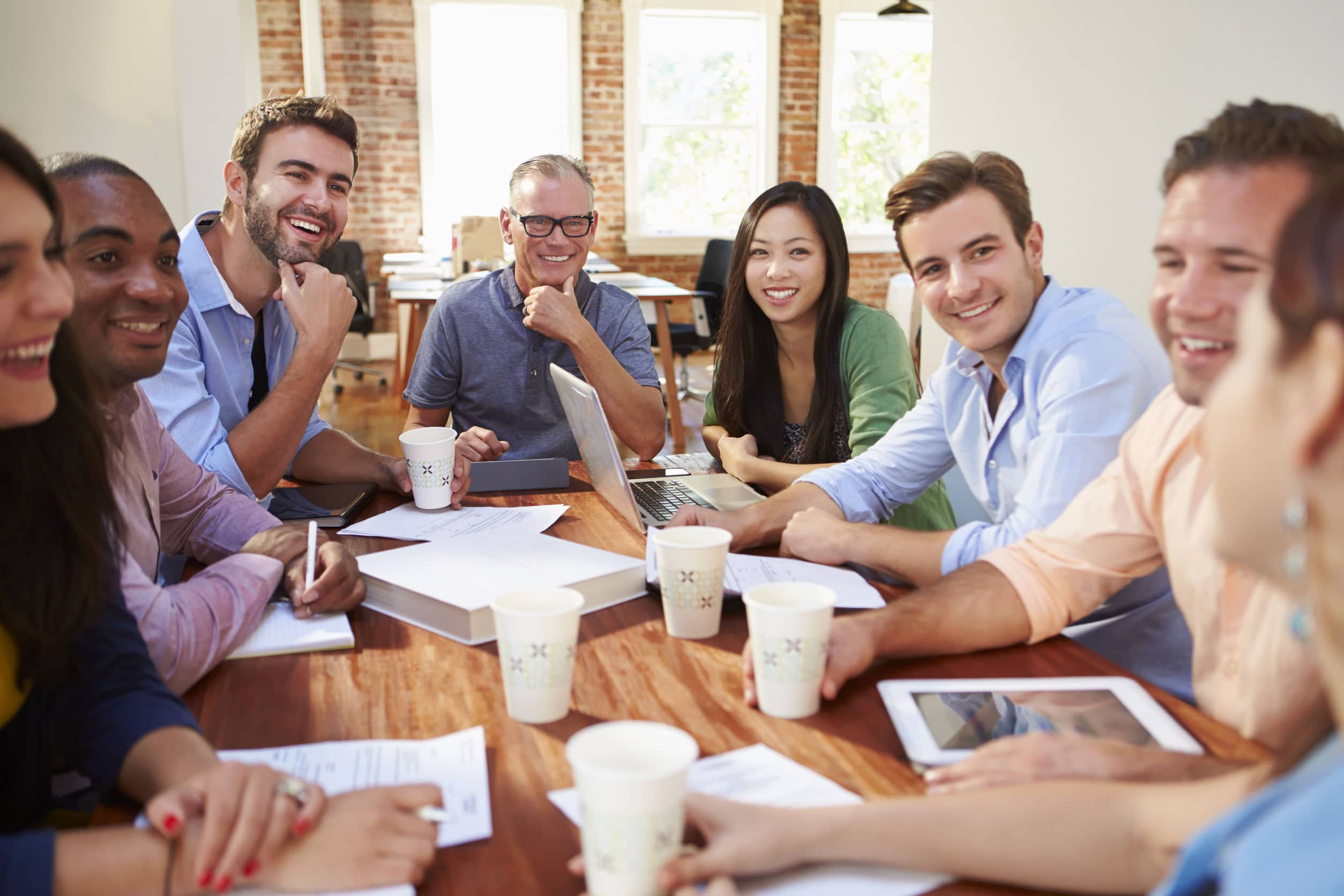 happy group of office workers in a meeting discussing ideas