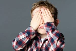 young child covering his eyes playing peekaboo