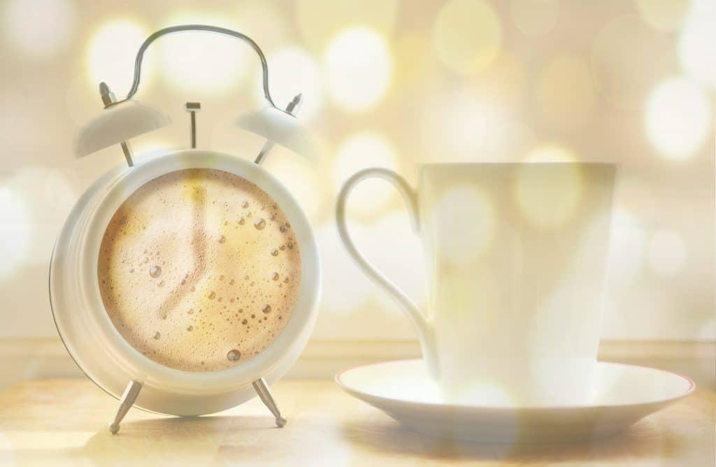 alarm clock beside a coffee cup