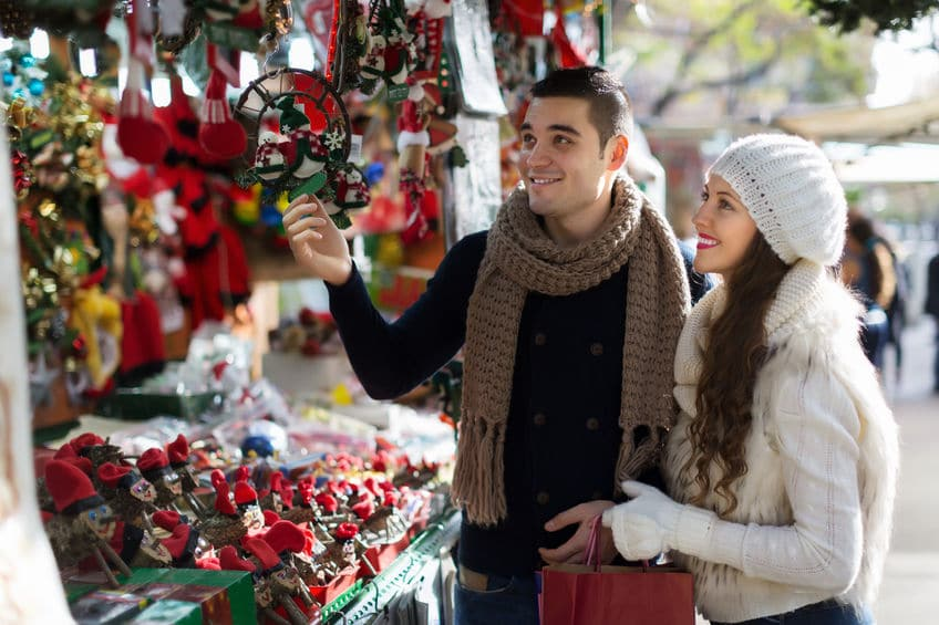 couple choosing christmas trinkets for souvenirs at a market in Barcelona
