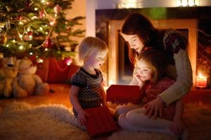 mother and her daughters looking at an open christmas gift