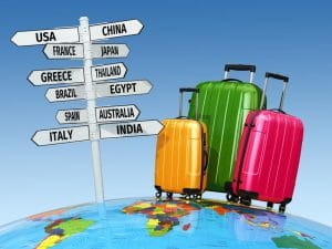 colored luggage beside a signpost of countries