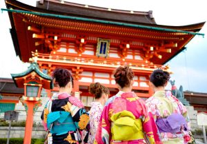 girl wearing Japanese kimono in front of a temple