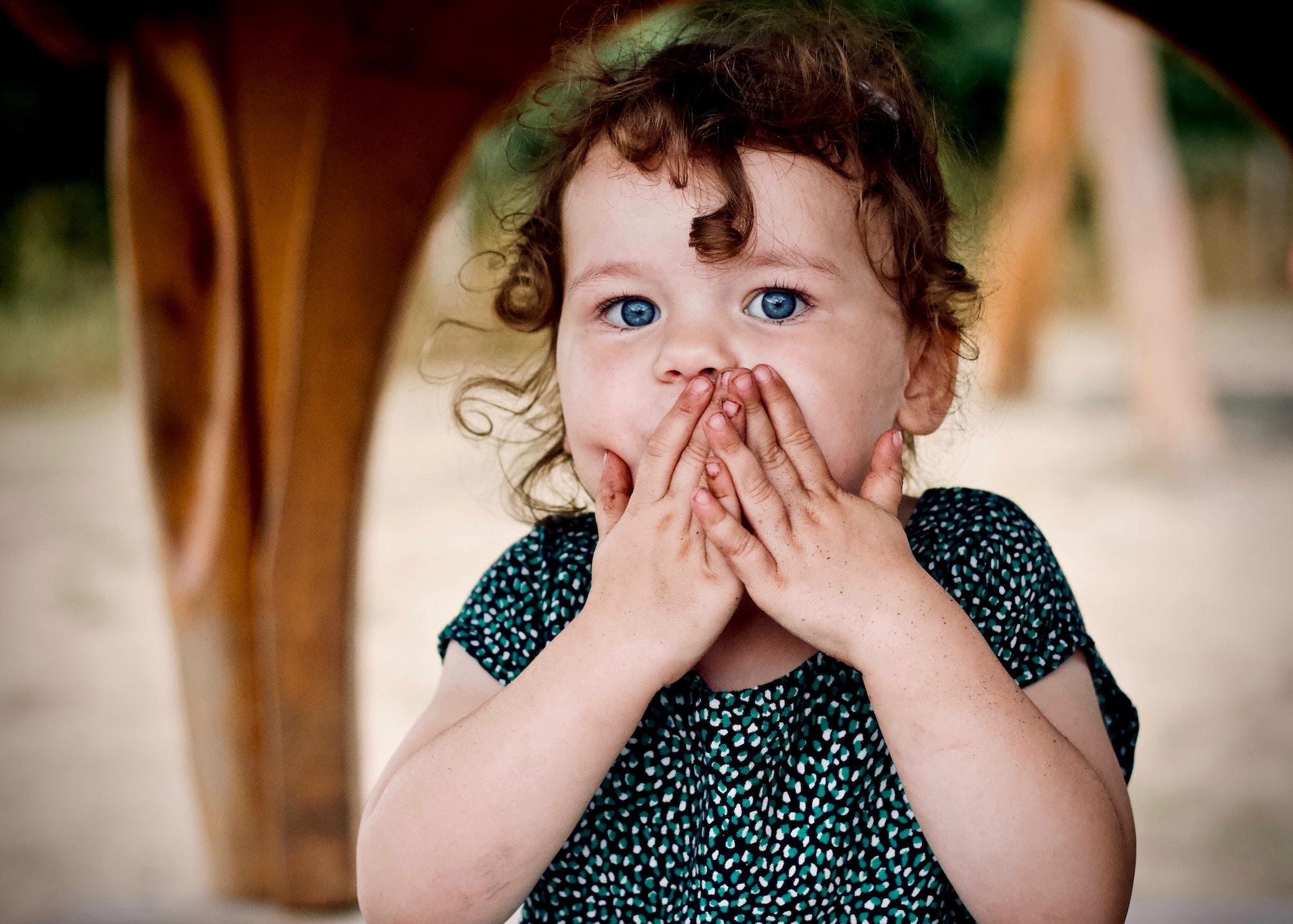 Little Girl Holding Her Lips