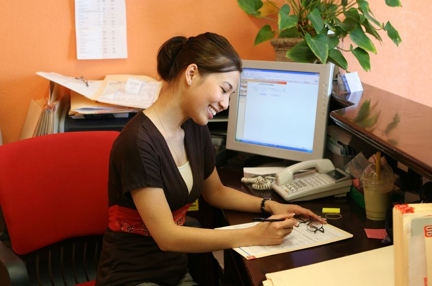 637455 - a woman receptionist working hard at the front desk