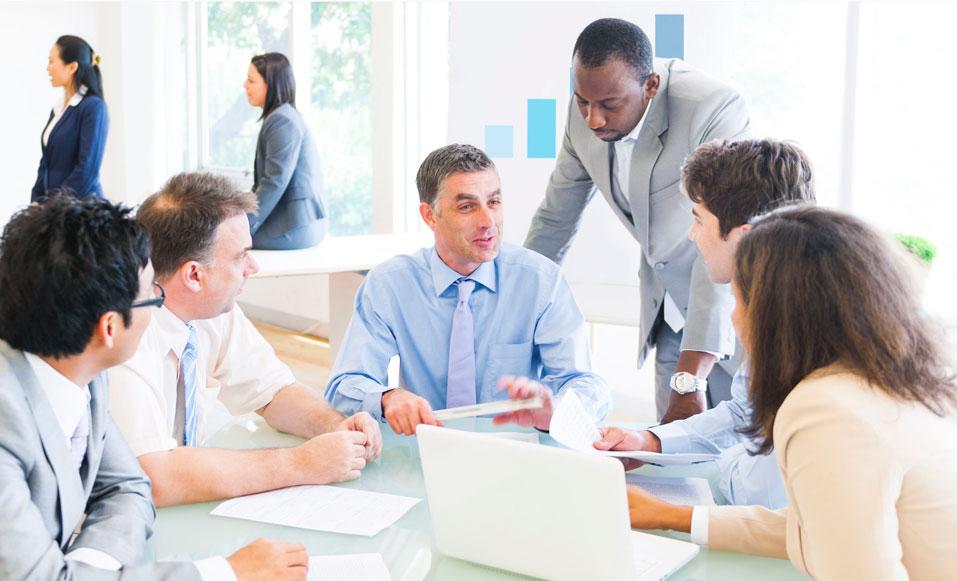 Seis profesionales al rededor de una mesa de oficina, todos vestidos formalmente y teniendo una reunión empresarial mientras dos mujeres profesionales entran a la oficina en el fondo de la imagen.
