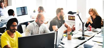 Profesionales de diversas nacionalidades en una oficina trabajando en optimización de motores de búsqueda
